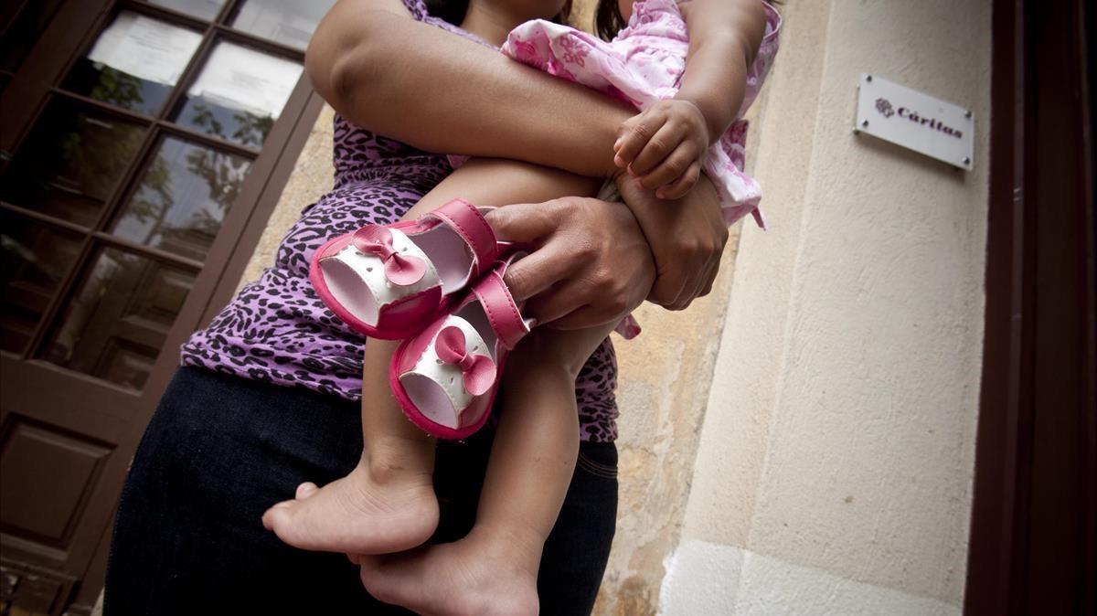 Una madre con su hija en brazos, en una foto de archivo