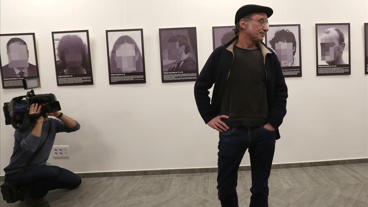 Santiago Sierra, junto a su instalación 'Presos políticos', la pieza que fue reirada de Arco la semana pasada y que el artista presentó ayer en la Fundación Estudios Libertarios Anselmo Lorenzo de Madrid.