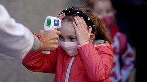 una profesora le toma la temperatura a su alumna, a la entrada del centro escolar.