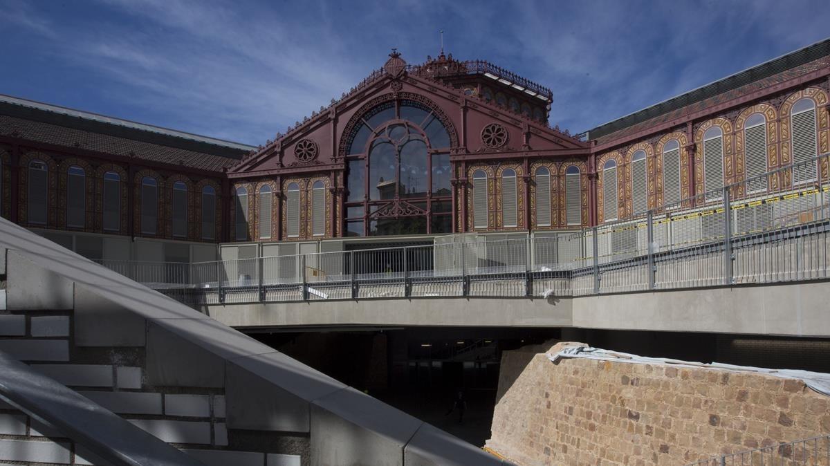 La fachada del mercado de Sant Antoni. En la parte inferior se puede ver la parte del foso medieval que se ha recuperado.