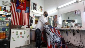 El barbero Germán espera clientes en su local decorado con banderas estadounidenses y una del Barça, en La Habana.