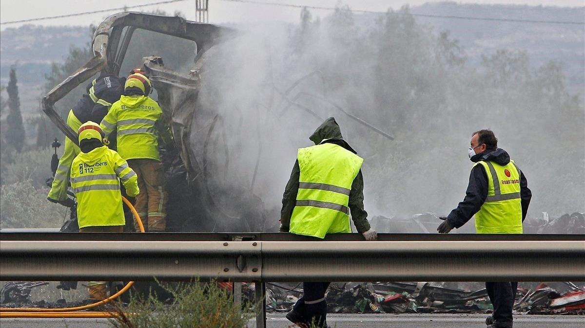 Operarios y bomberos trabajan en el lugar del accidente registrado esta madrugada en la autovia A-7 a su paso por el municipio alicantino de Crevillent.