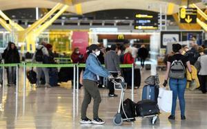 Pasajeros en un aeropuerto con mascarilla por el coronavirus.