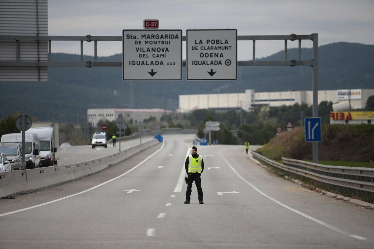 Un agente de los Mossos vigila el acceso a Igualada, confinada por el coronavirus.