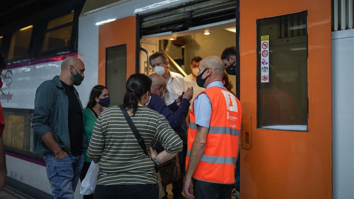 Pasajeros y un informador de Rodalies junto a un tren, en la estación de Sants.