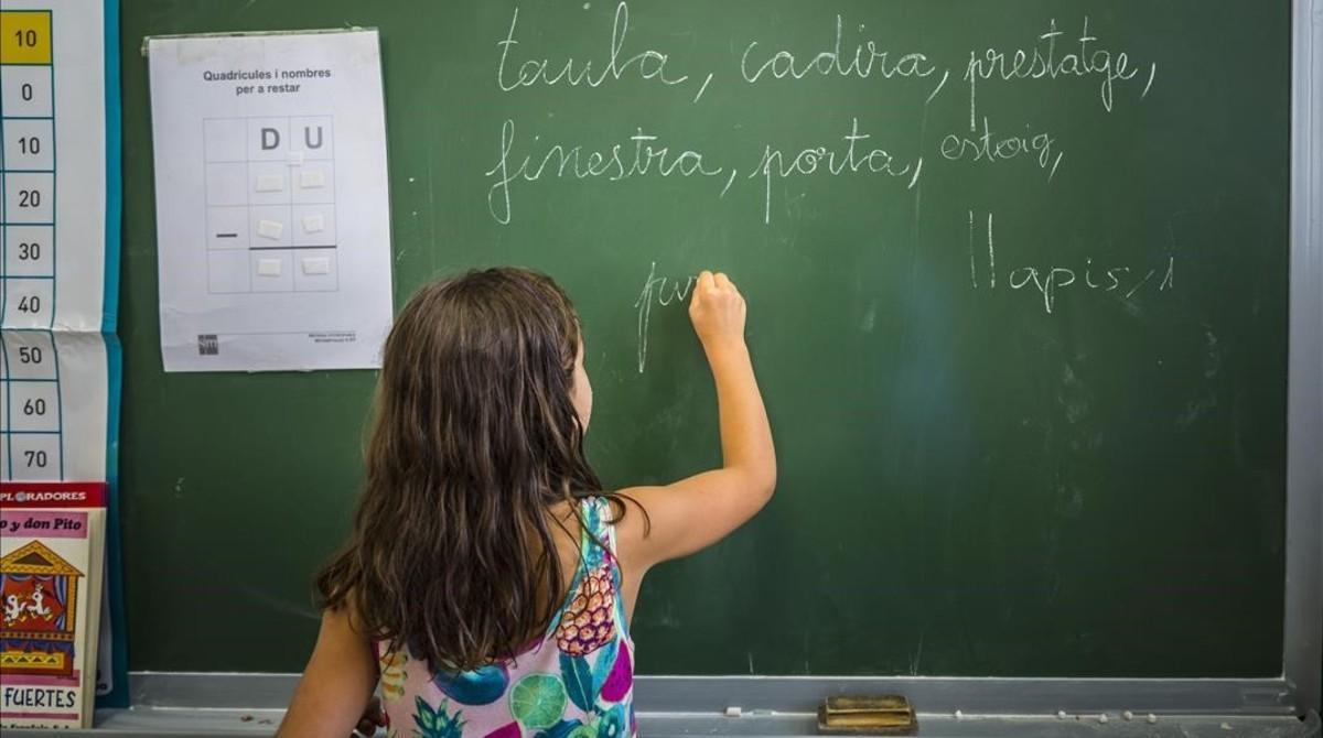 Una niña escribe en la pizarra, en una clase del colegio público Jaime Balmes, en València, el pasado julio.
