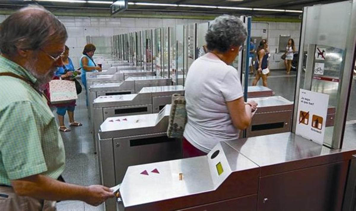 Varios usuarios validan sus billetes en las máquinas de la estación de metro de Plaça Universitat, en Barcelona, ayer.