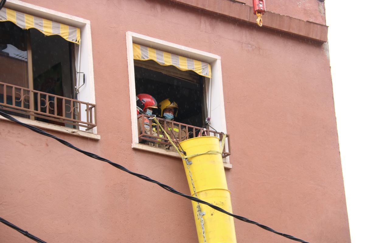 Dos Bombers en la ventana del inmueble afectado por el hundimiento
