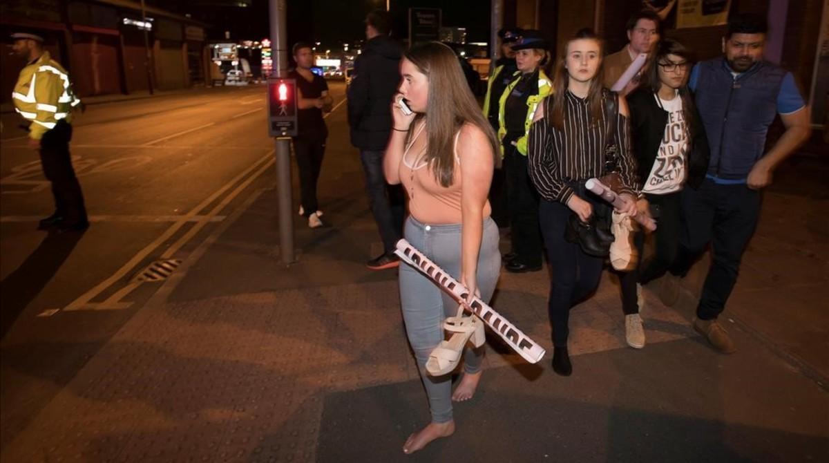 Asistentes al concierto de Ariana Grande salen tras la explosión en el Manchester Arena.