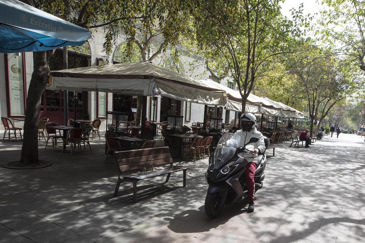 Una moto circula por la peatonal Enric Granados junto a una macroterraza, este miércoles.
