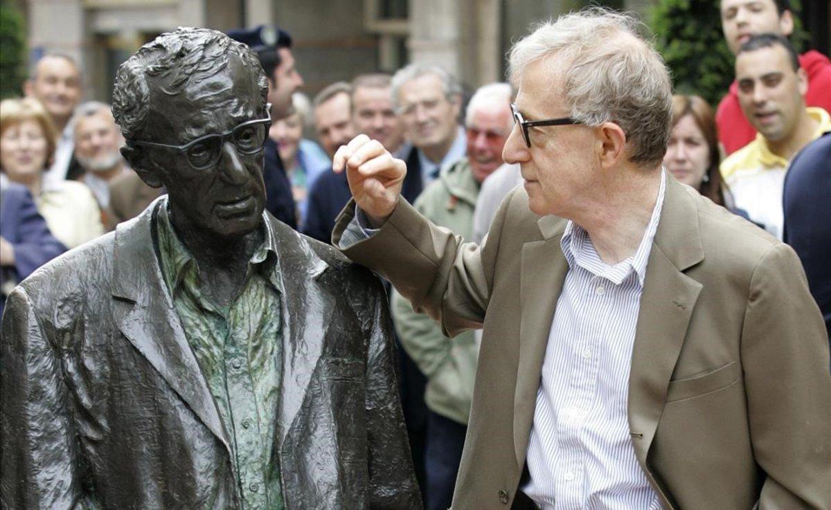 El cineasta Woody Allen posa junto a su estatua en Oviedo.