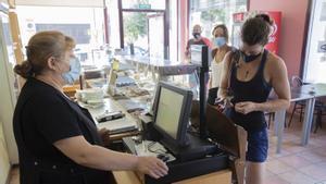 Una mujer paga en efectivo en la panadería-cafetería Aimar, de Cornudella de Montsant, pueblo sin cajeros automáticos.