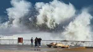 Un grupo de persona observa la fuerza de las olas en la playa de La Barceloneta.