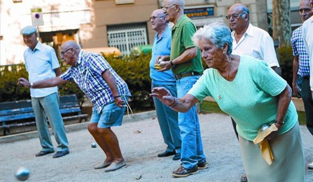 Un grupo de pensionistas juega a petanca en un parque de Barcelona.