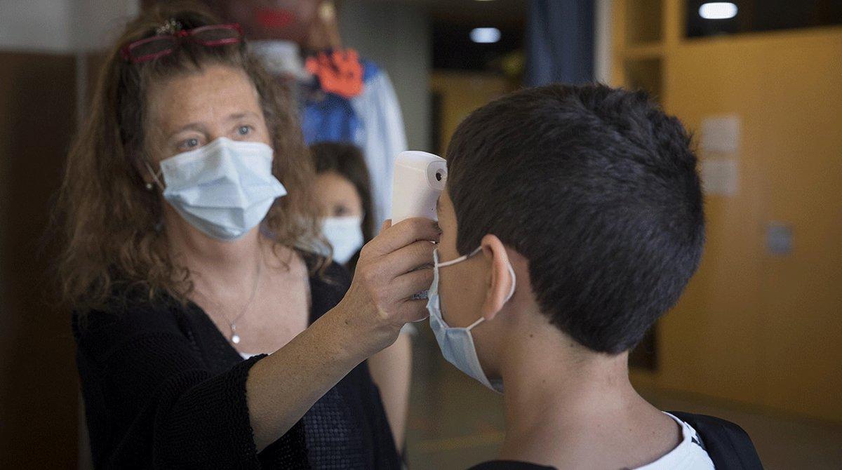 Una profesora del Institut Escola Antaviana de Barcelona comprueba la temperatura de un alumno, el pasado 15 de junio.