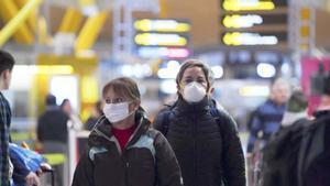 Sanidad confirma 11.178 casos de coronavirus y 491 muertos en España. En la foto, pasajeros con mascarilla en el Aeropuerto de Madrid-Barajas.
