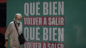 Uh hombre pasea por València tras un cartel que celebra la nueva normalidad.