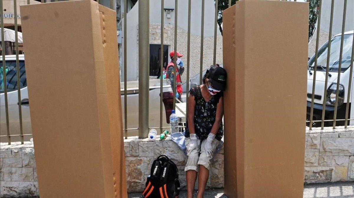 Una mujer llora a un familiar junto a unos ataúdes de cartón en Guayaquil.