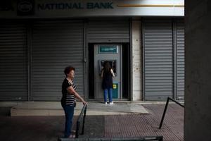 Una mujer retira dinero de cun cajero ayer en Atenas tras tres semanas de control de capitales.