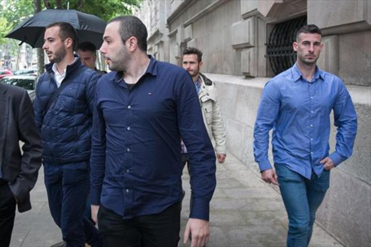 Cuatro de los mossos imputados salen del palacio de Justícia, ayer.