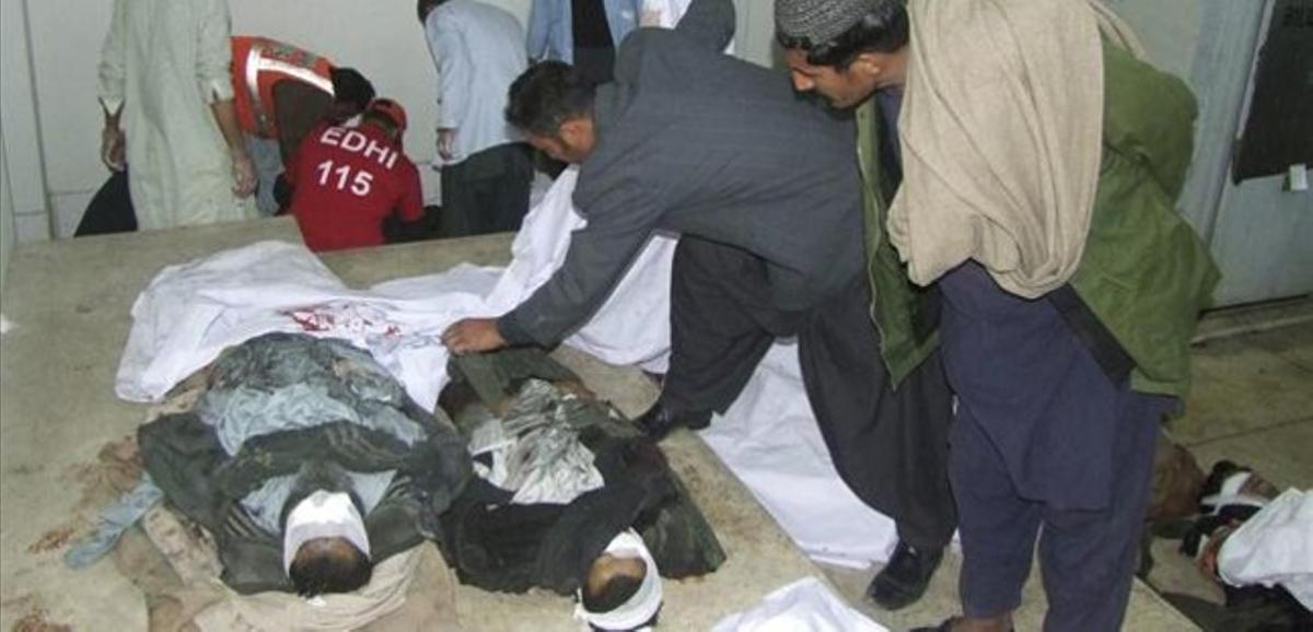 Dos hombre observan a dos de los fallecidos en uno de los atentados de Quetta.