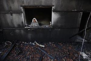 Un home inspecciona la casa atacada pels colons on va morir cremat el nen de 18 mesos a la localitat palestina de Duma.