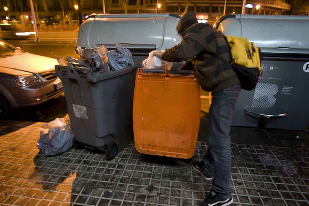 Un joven busca comida en un contenedor de basura orgánica, en Barcelona.
