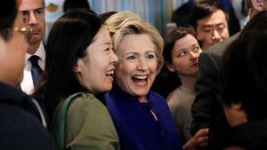 Clinton (centro) saluda a la audiencia durante una visita al restaurante Kung Fu Tea, en Queens (Nueva York), este lunes.