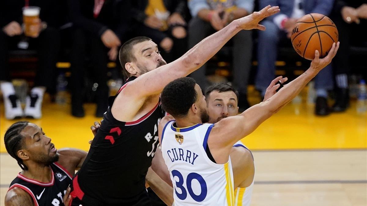 Gasol trata de taponar una acción de Curry.