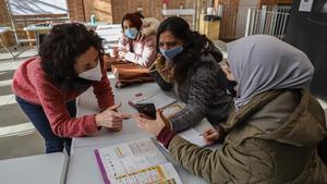 Unas madres charlan con una de las profesoras del taller de La Troca.