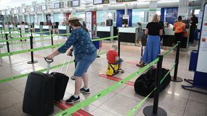 Una familia de turistas británicos, en el aeropuerto de El Prat, a punto de volar de regreso a Londres, este lunes 27 de julio.