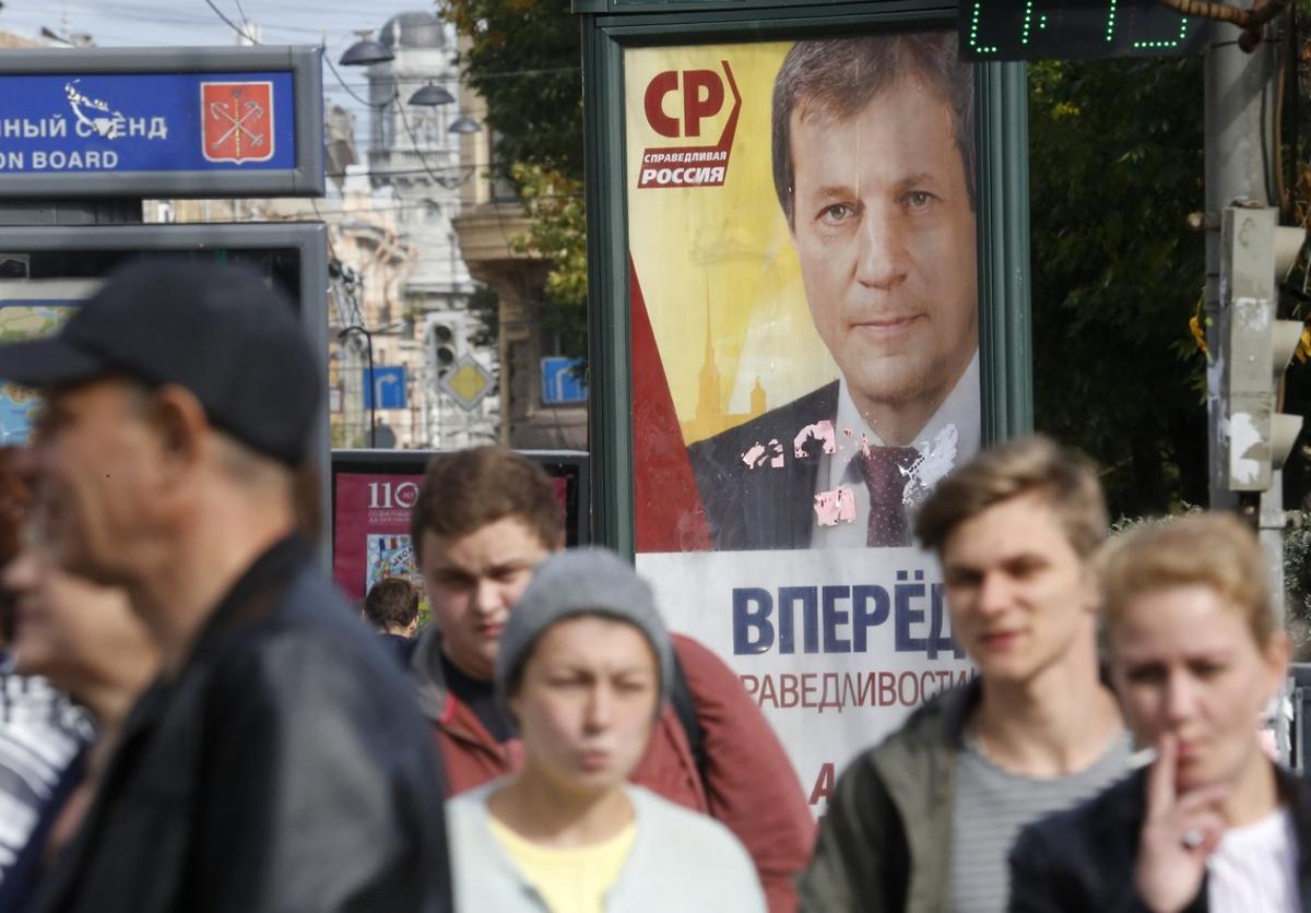 Peatones pasas por delante de un cartel electoral en San Petersburgo.