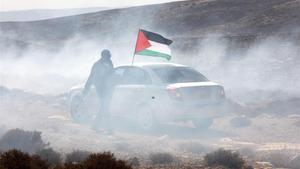 Un hombre ondea la bandera palestina entre gas lacrimógeno, este domingo durante una protesta en el pueblo cisjordano de Shiyoukh, cercano a Hebrón.