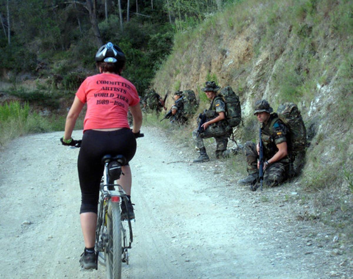 Una ciclista pasa ante soldados en pleno ejercicio de prácticas de combate.