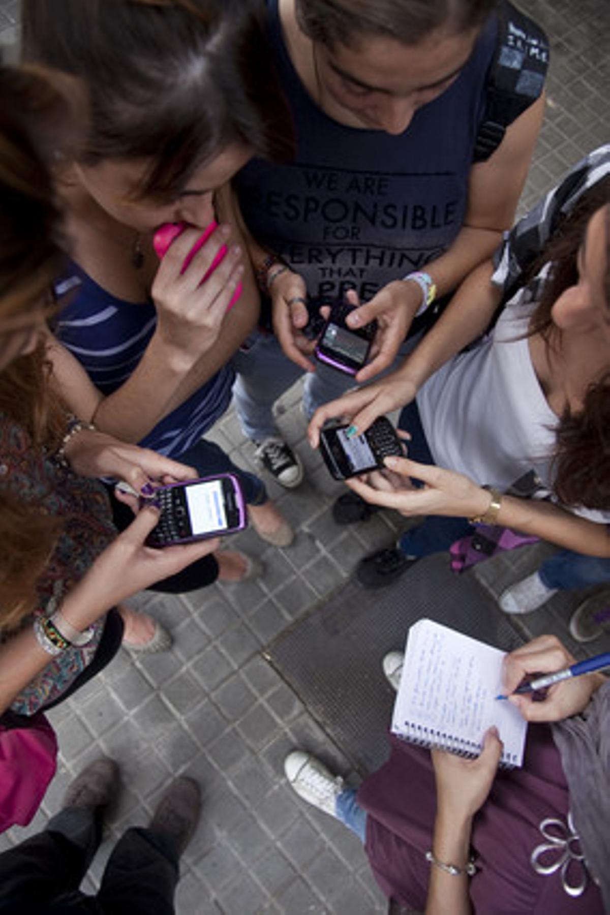 Varias adolescentes chatean con sus Blackberry.