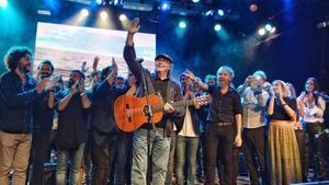 Serrat saluda al público asistente al concierto de Som Música Directa en Luz de Gas rodeado de otros cantantes y grupos.