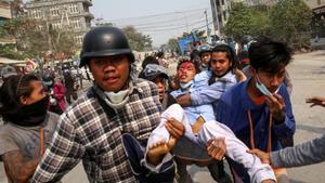 Un grupo de manifestantes carga con un joven herido en una protesta contra la junta militar en la ciudad de Mandalay este lunes.