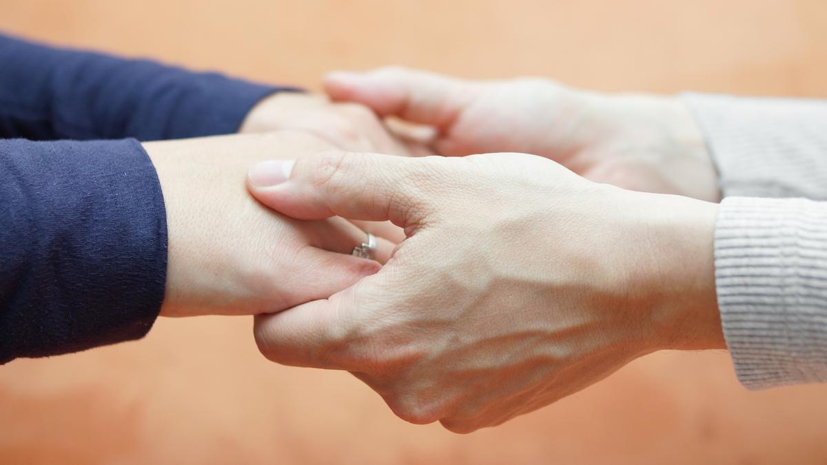 Dos personas se cogen de las manos.