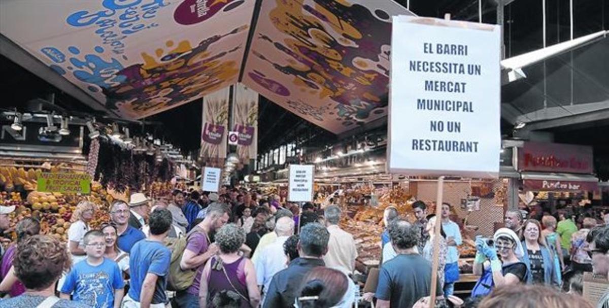 Protesta en la Boqueria 8 Un grupo de barceloneses, ayer, porta pancartas contra la reconversión de la instalación por el turismo masivo.