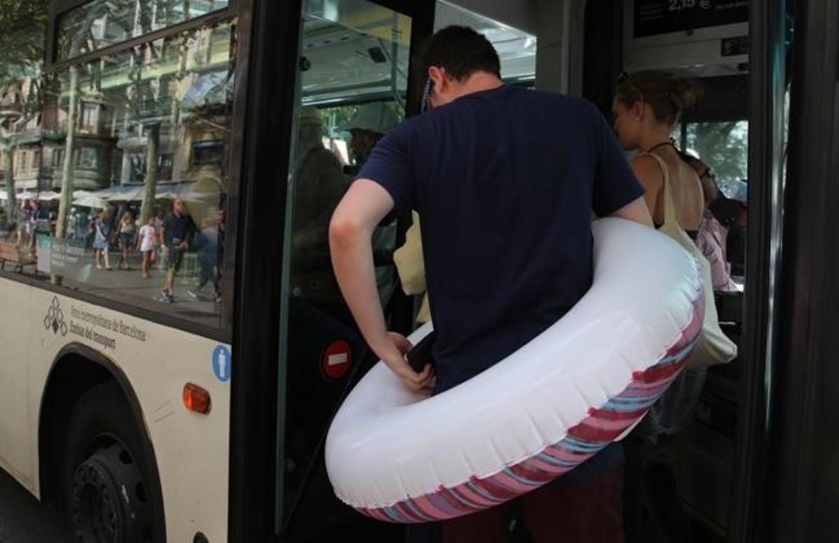 Un hombre con flotador incorporado trata de entrar en un bus lleno en el paseo de Joan de Borbó.