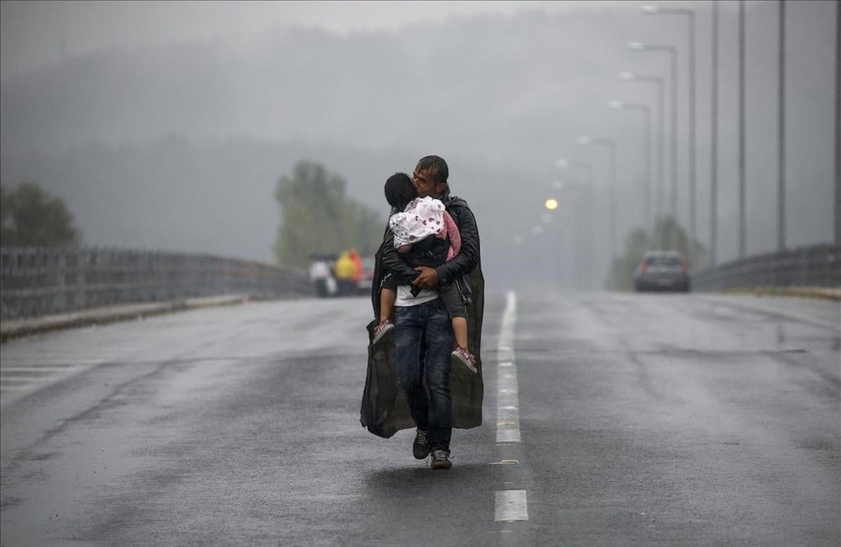 PREMIOS PULITZER Unrefugiado sirio besa a su hija mientras camina en mediode una tormenta hacia la frontera de Grecia s con Macedonia.