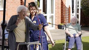 Una trabajadora de una residencia de Leicester observa a una anciana mientras lanza un arco.