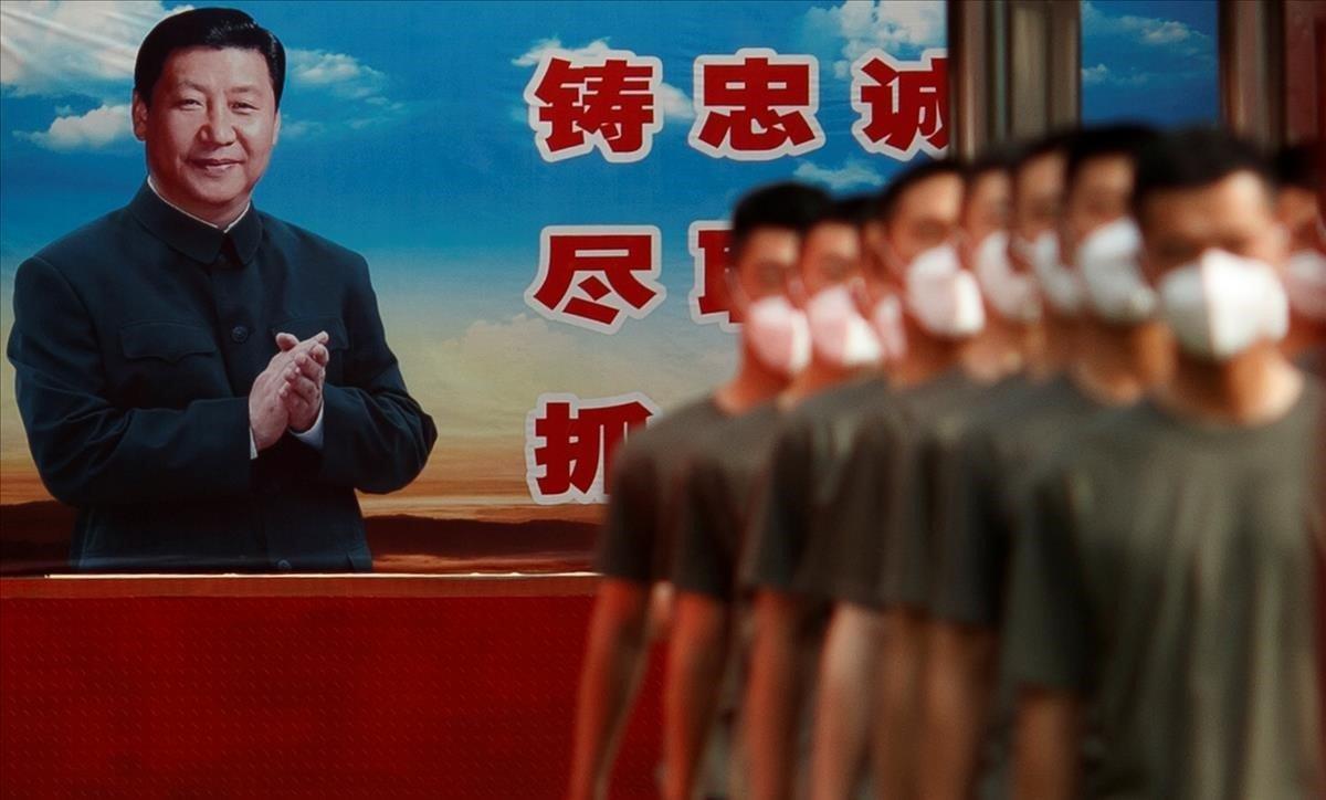 Agentes de la policía paramilitar china marchan en formación ante un cartel del presidente chino, Xi Jinping, en el día inaugural del primer Congreso Nacional del Pueblo tras la declaración de la pandemia por coronavirus.