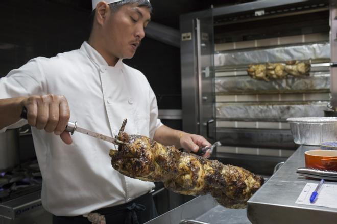 Un cocinero del restaurante barcelonés La Brochette prepara unos pollos a l'ast.