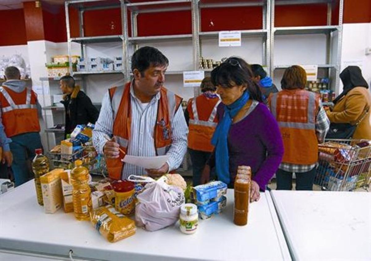 En el local 8 El voluntario José María Gallardo ayuda a María Dolores Segarra a recoger un lote, el miércoles.