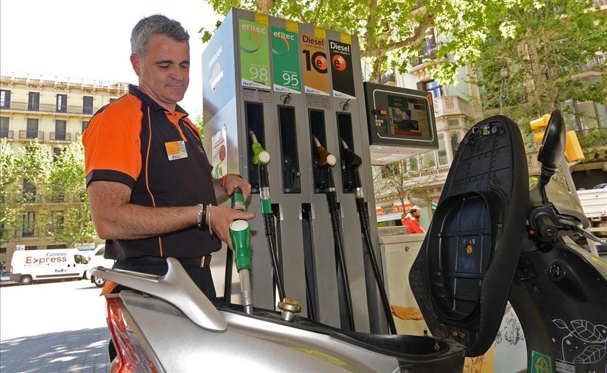 La energía acelera la inflación en España hasta el 2,2 % en abril. En la foto, un empleado de una gasolinera pone combustible en una moto, en Barcelona.