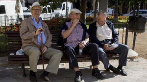 Tres jubilados descansan en un banco de un parque en Valencia.
