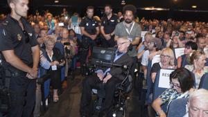 GRA059 ARONA (TENERIFE), 01/07/2016.- El físico británico Stephen Hawking custodiado por tres agentes de la Policía nacional durante su asistencia al Festival Starmus el pasado miércoles, tras recibir amenazas de muerte por parte de una mujer estadounidense que ha sido detenida en Arona (Tenerife) por supuestos delitos de acoso y amenazas al científico. EFE/Ramón de la Rocha