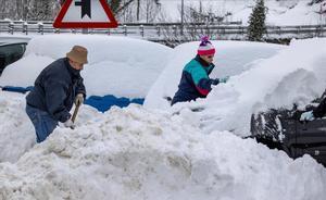 Unos vecinos quitan nieve de sus coches en el pueblo de Pajares.