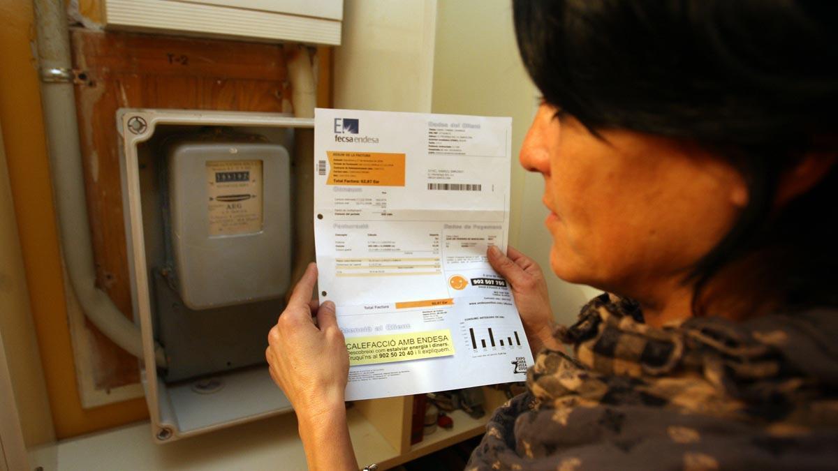 Los precios ahondan su caída en octubre con un descenso del 0,9 % por la luz. En la foto, una mujer consulta una factura eléctrica junto a un contador de la luz.